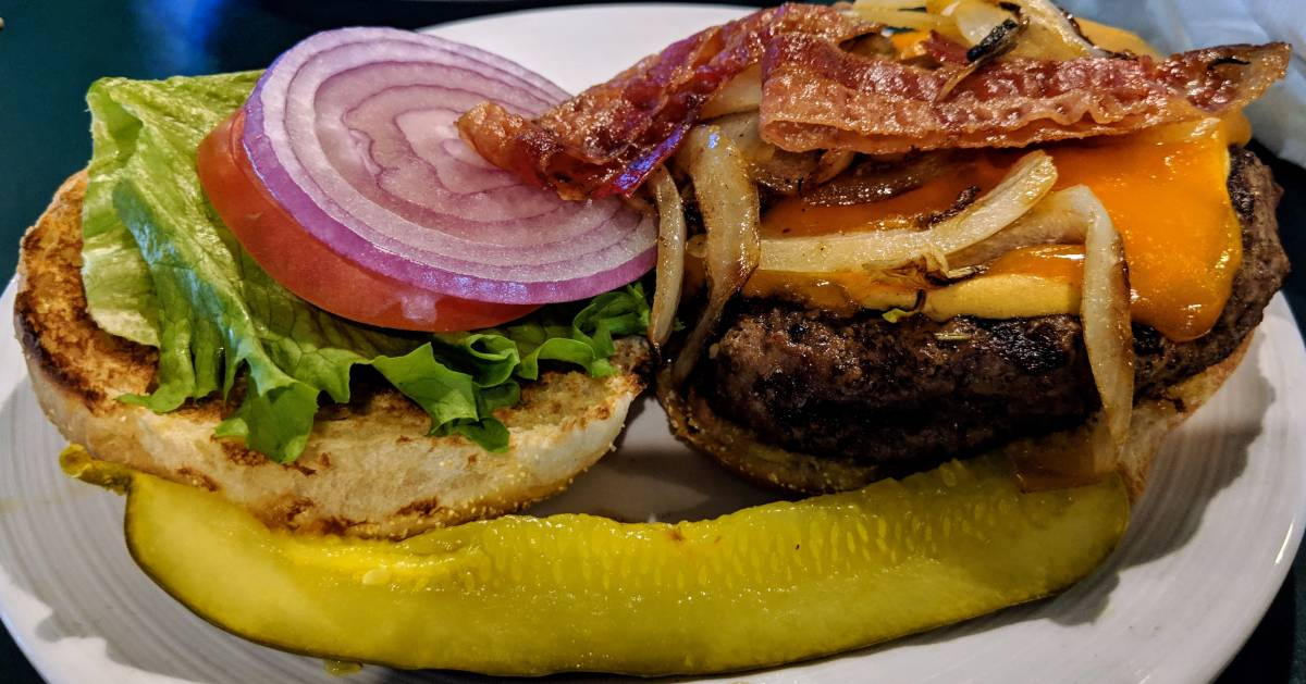 open burger with bacon, pickle in front