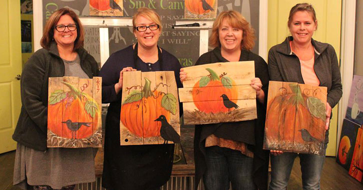 four women holding up paintings of a pumpkin