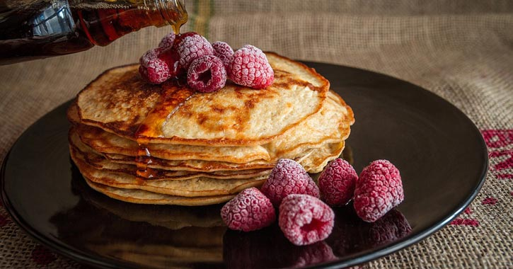 pancakes, syrup, and berries on a plate