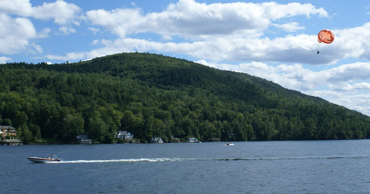 a boat on lake george towing parasailers