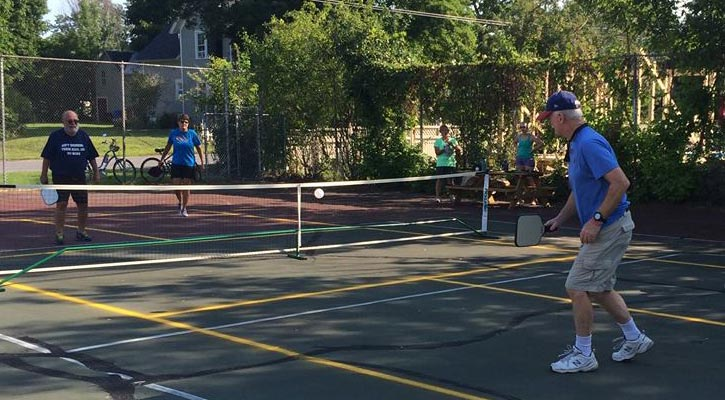 four people playing pickleball on an outdoor court