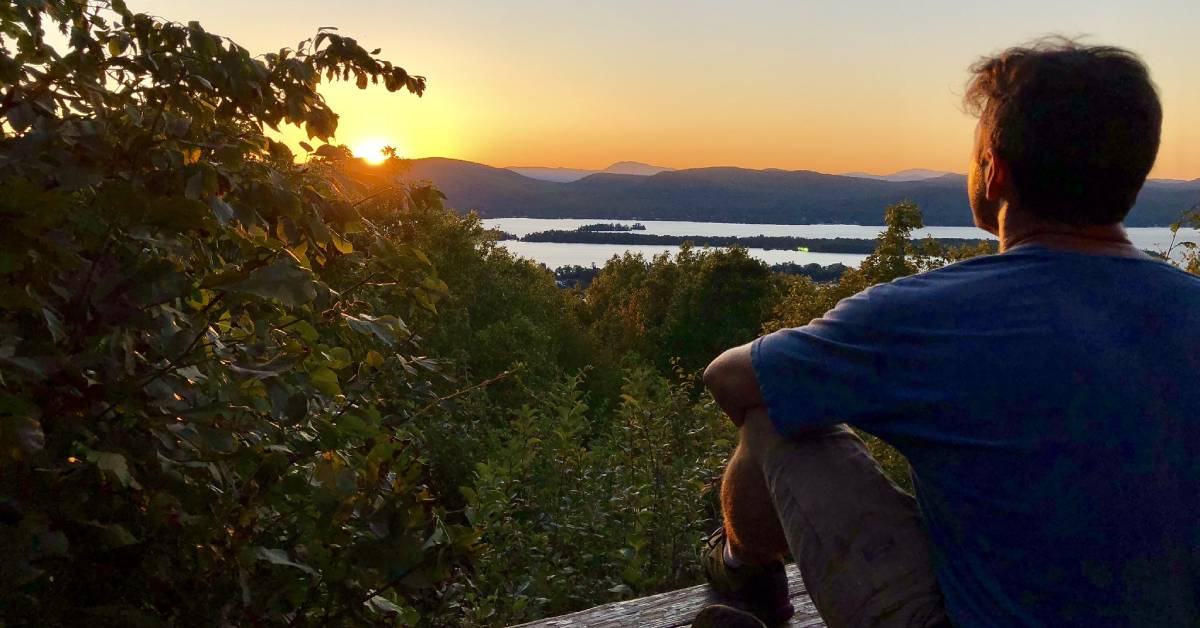 man sitting on wooden platform looking at sunset over lake