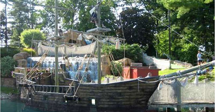 a large pirate ship on water in a mini-golf course
