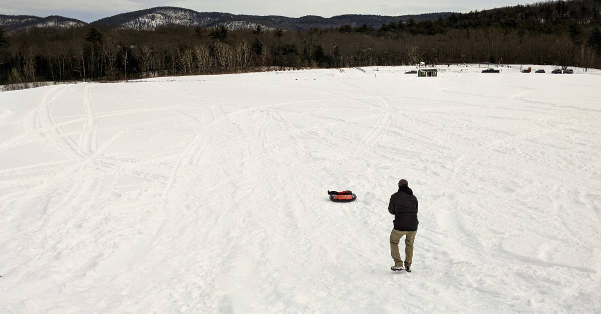 man standing near kid sliding down a hill in a snow tube