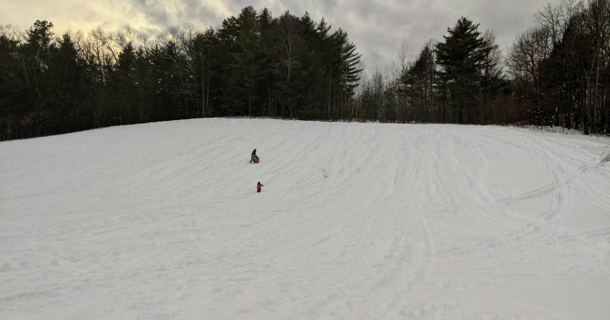 large tubing hill, two people on it
