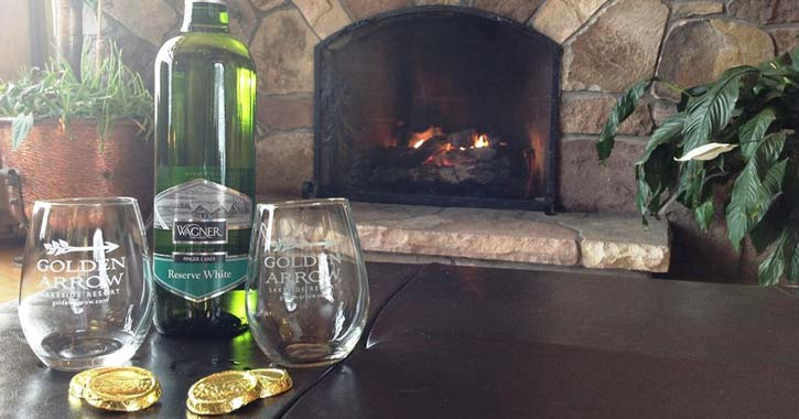 wine and a pair of glasses in front of the fireplace at the golden arrow resort