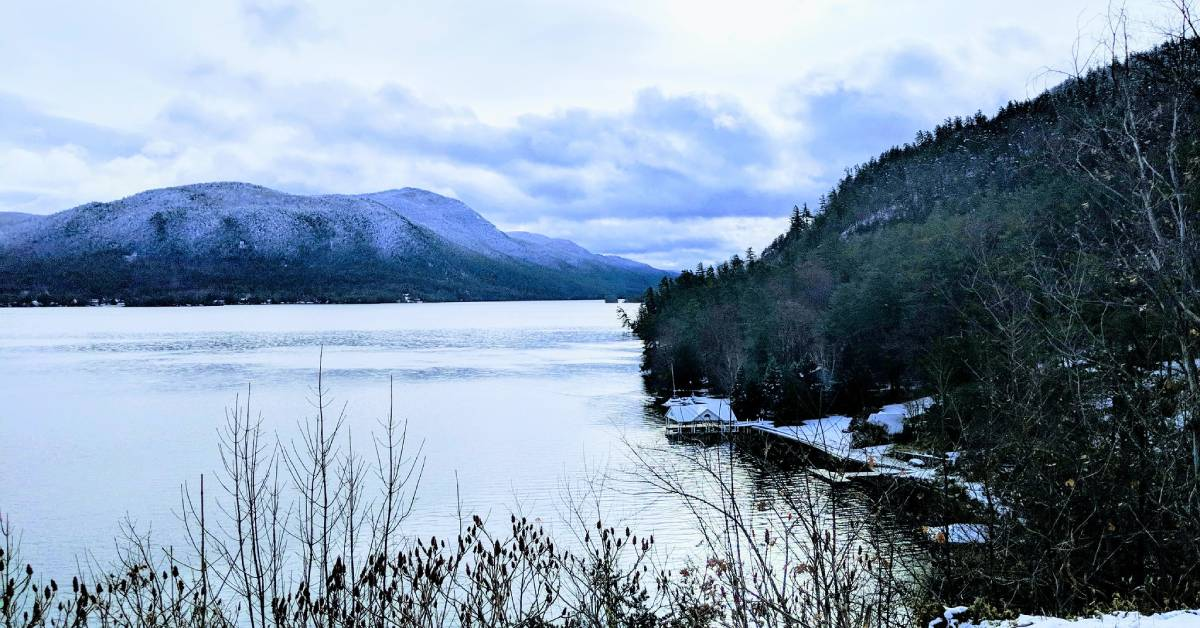 view of a lake and a snow covered mountain in winter