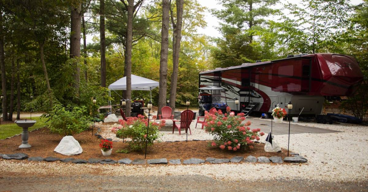 red rv at a campsite with chairs around a fire ring