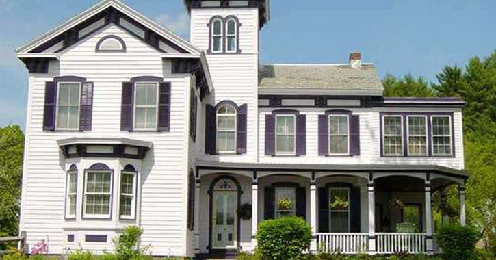 the outside of the bed and breakfast, white with dark purple shutters