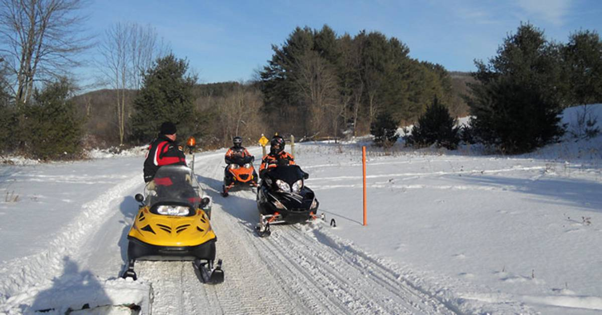 three snowmobilers on a trail