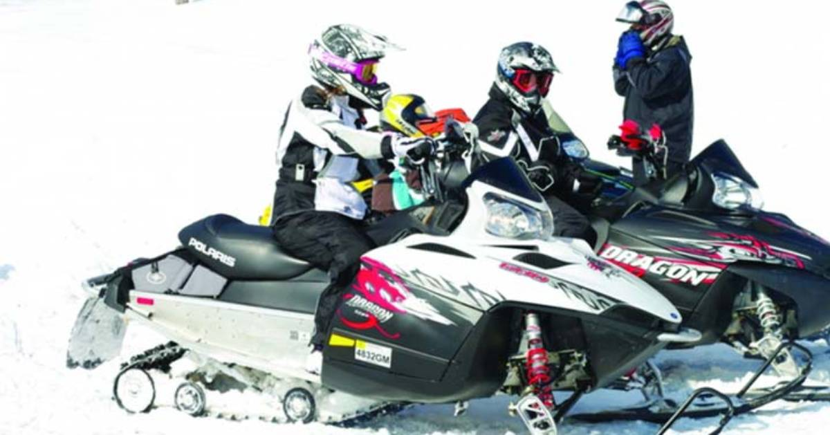 a small group of snowmobilers