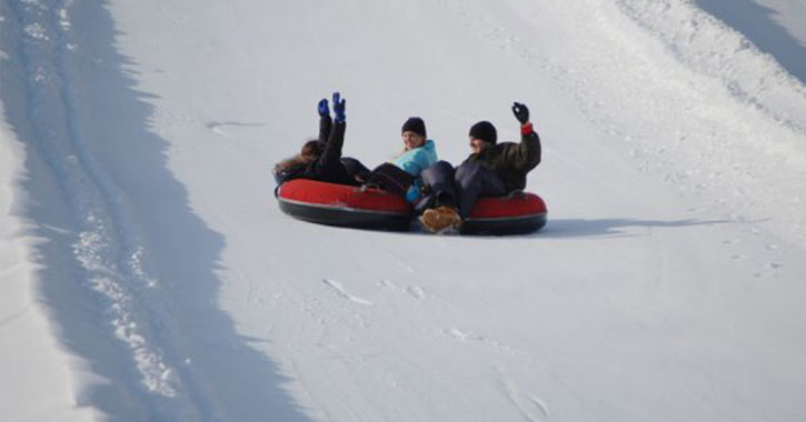 people riding down three snow tubes