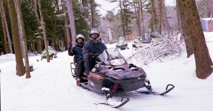 snowmobilers driving on a trail in the snow