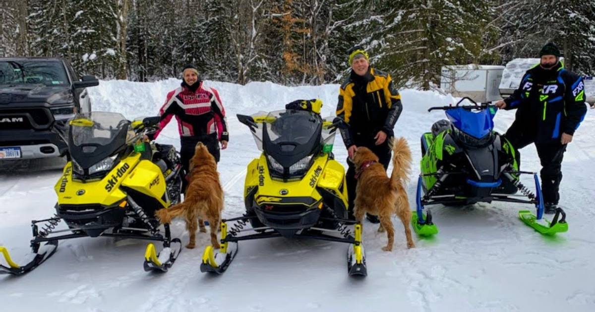 three men with their snowmobiles, two dogs