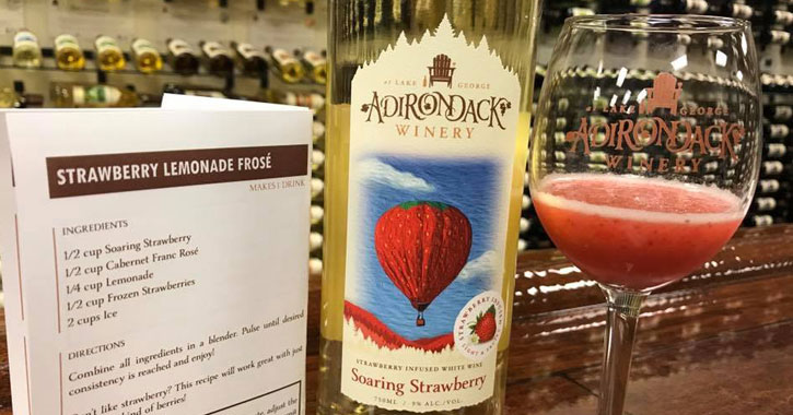 Adirondack Winery Soaring Strawberry bottle next to wine glass with cocktail and a recipe sheet