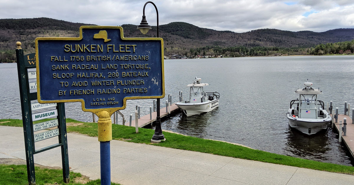 Sunken Fleet sign by water with boats