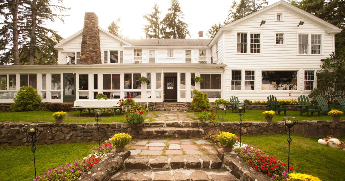 a white bed and breakfast with a stone wall and a stone chimney and green Adirondack chairs out front
