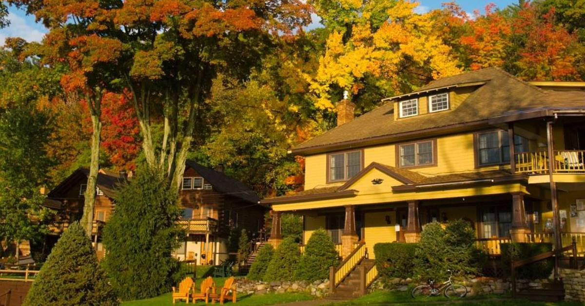 cottage and Adirondack chairs among fall foliage