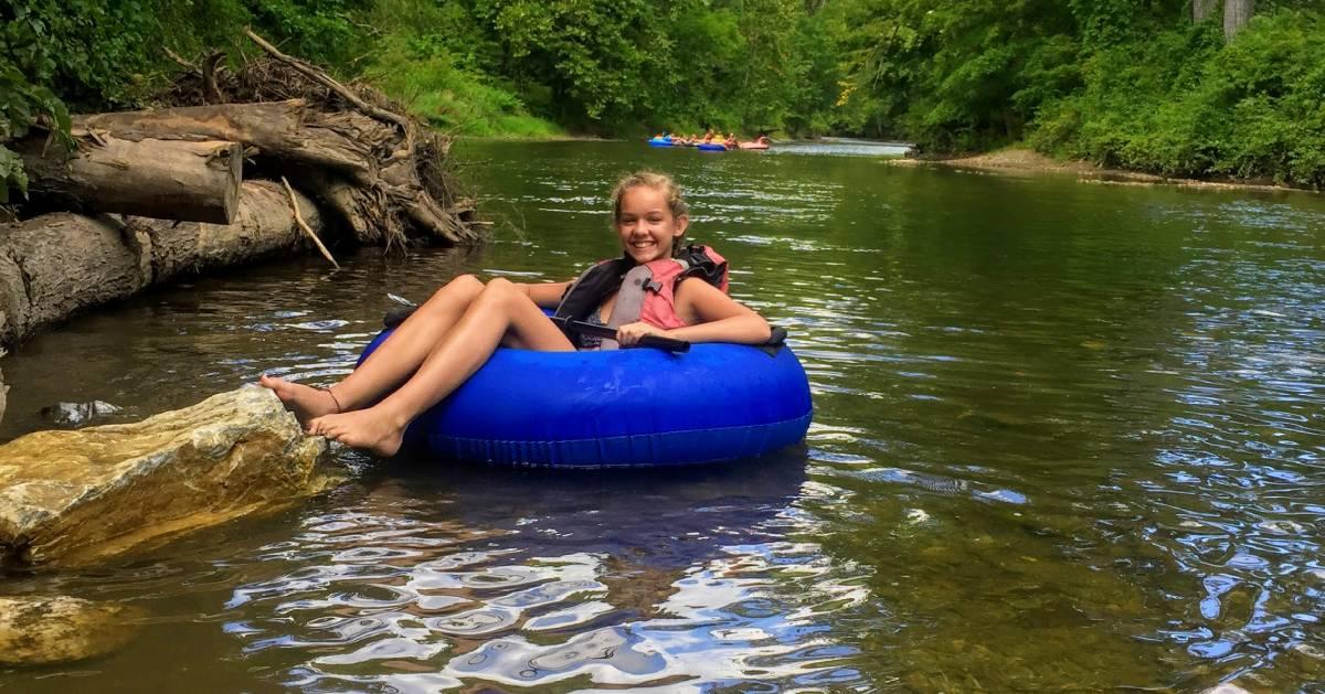 girl tubes on river