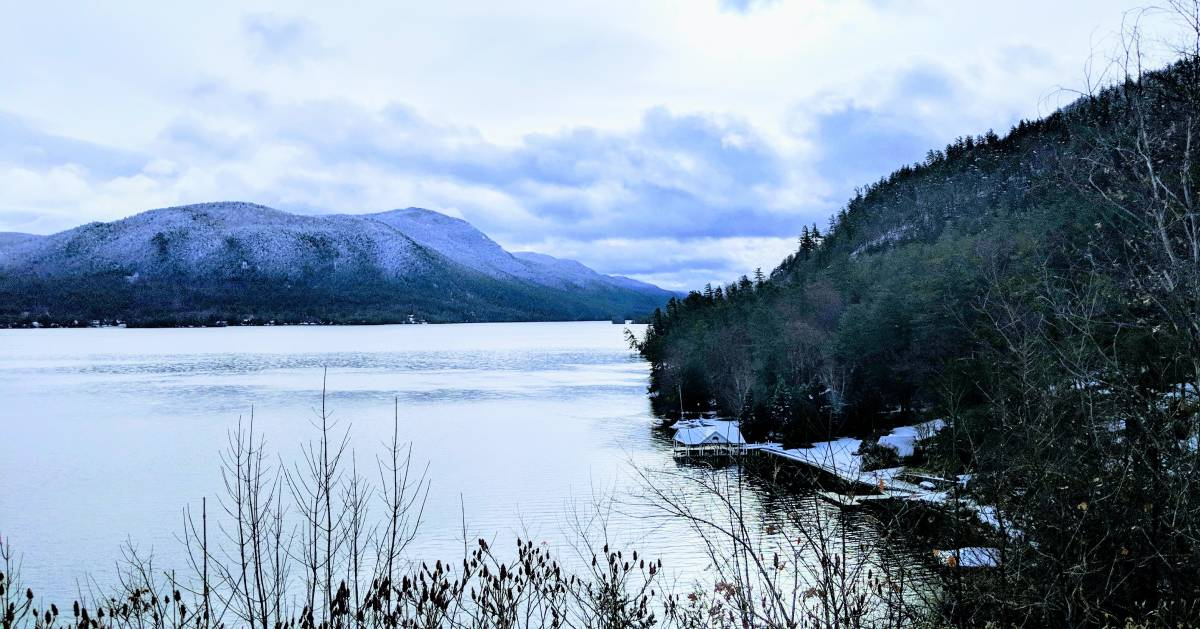 a beautiful view of a lake with mountain and trees in the winter