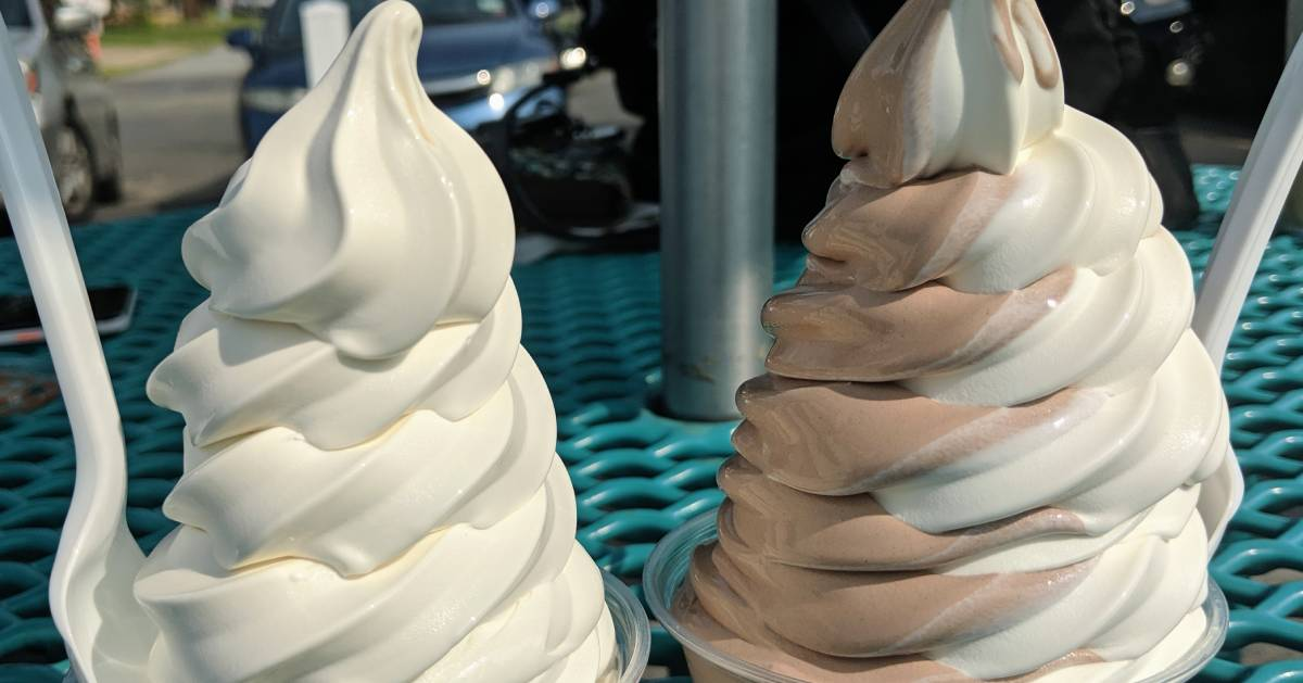 two soft serve ice cream dishes on a patio table