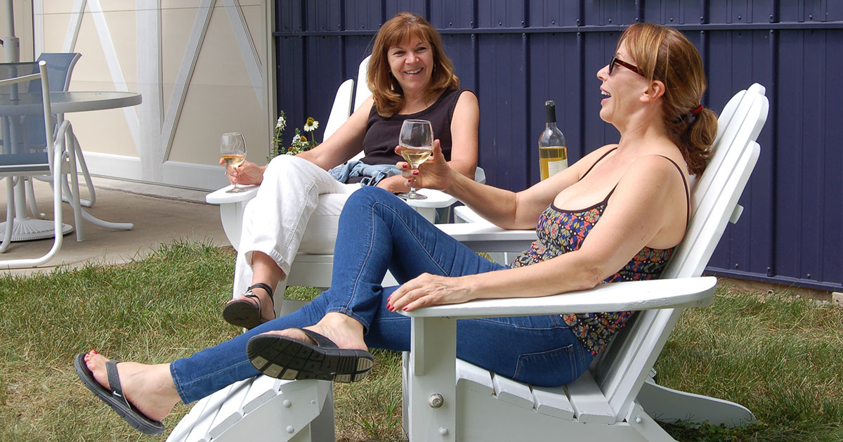 two women sitting with wine glasses