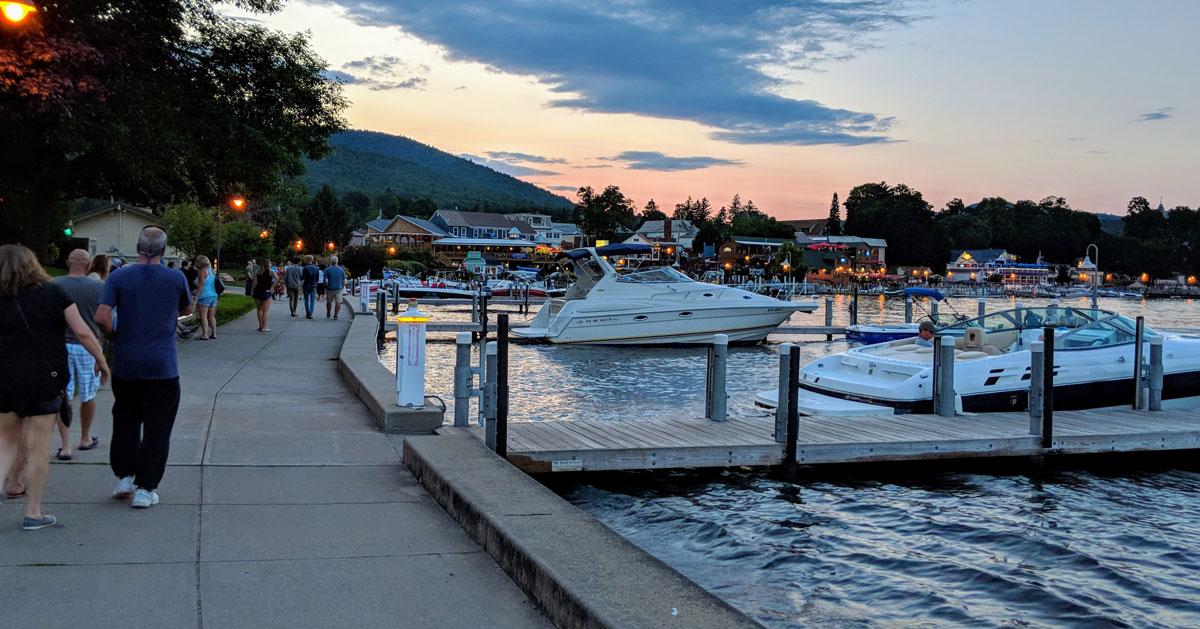 people walking by lake at dusk