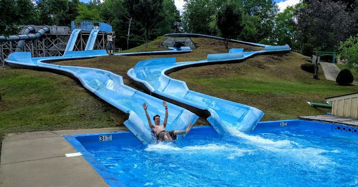 a man going down a waterslide with his arms up