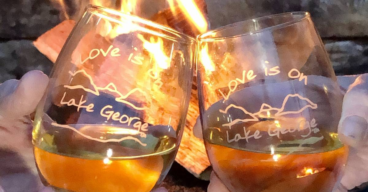 two wine glasses in front of a fire