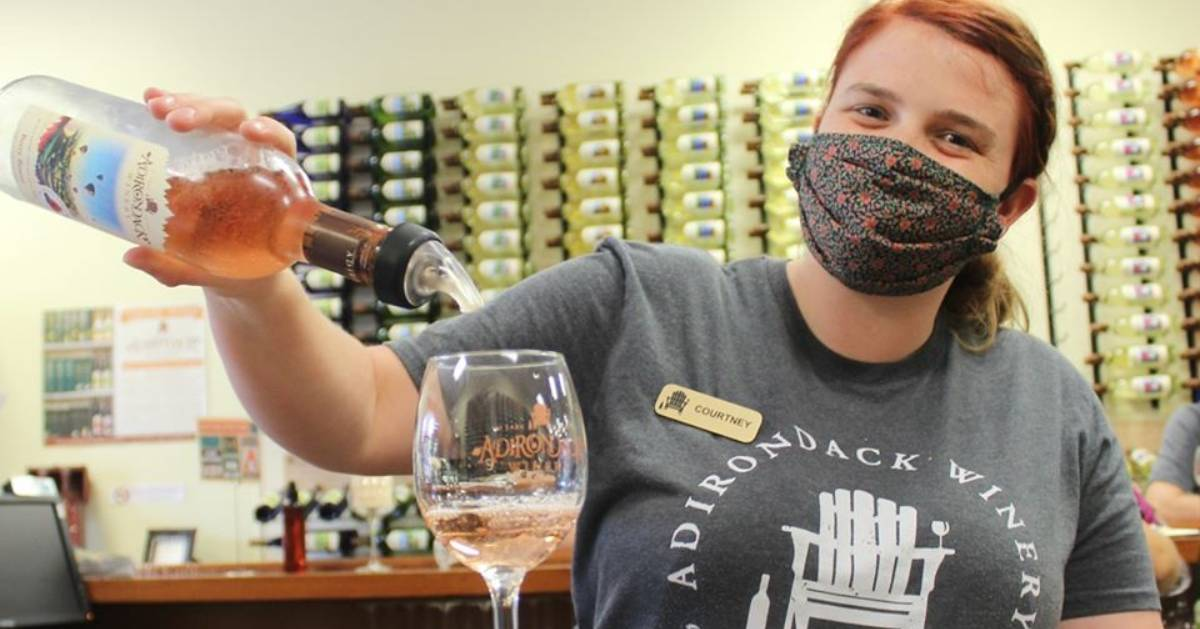 masked woman pouring wine