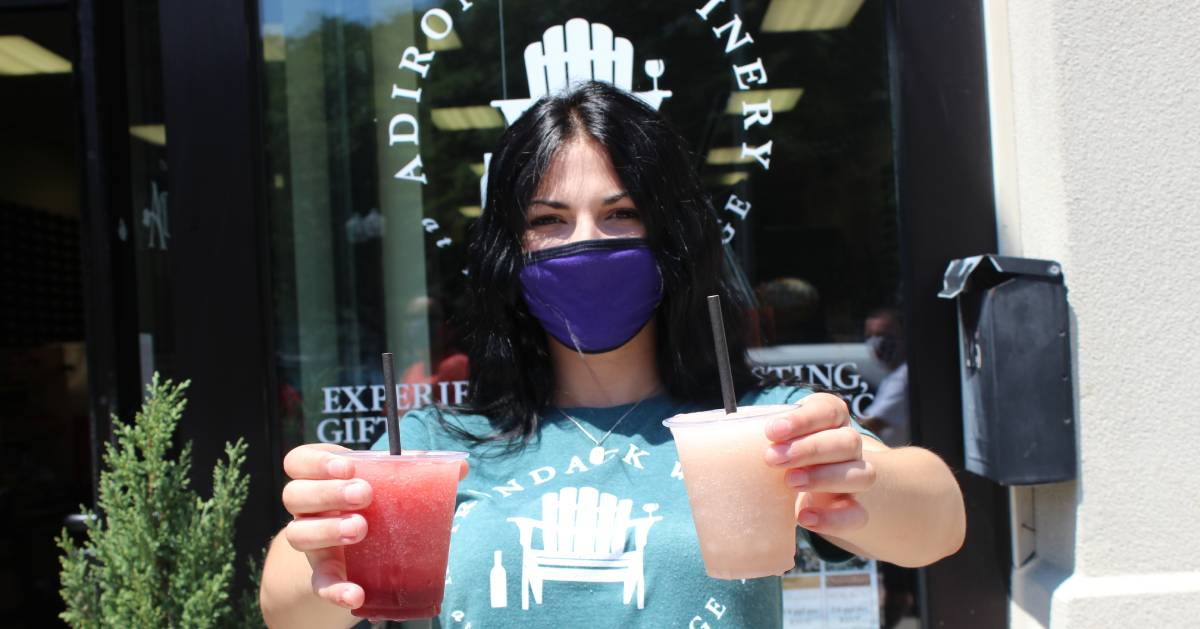 masked woman in front of winery holding up wine slushies