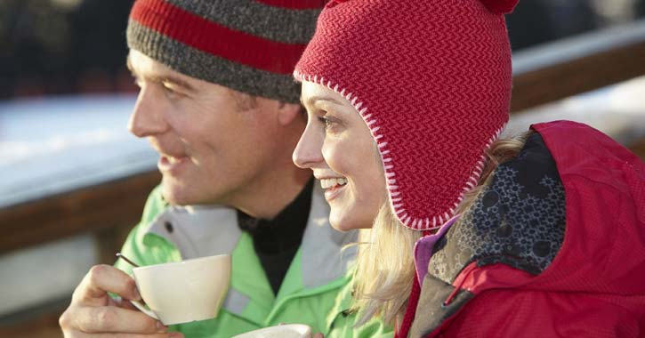 man and woman with winter hats and warm drinks