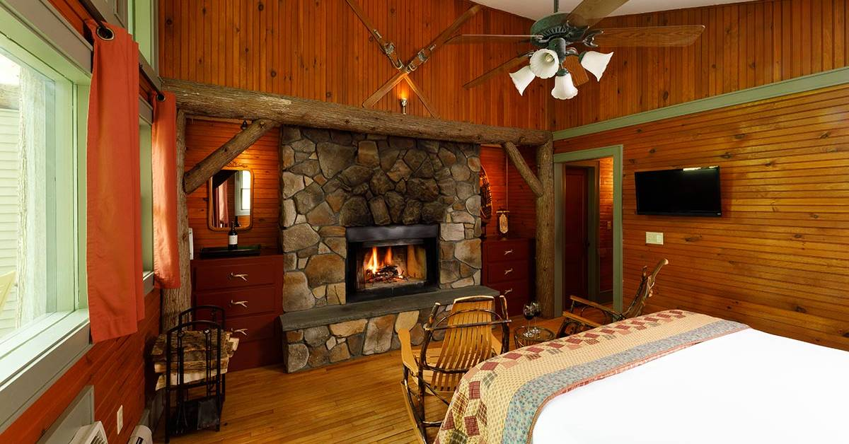 a guest room with wooden walls and floor, a bed, a stone fireplace, and chairs