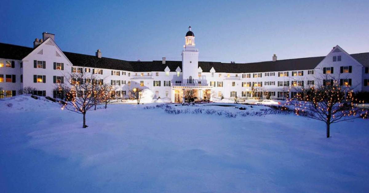 a large white hotel with snow on the ground outside
