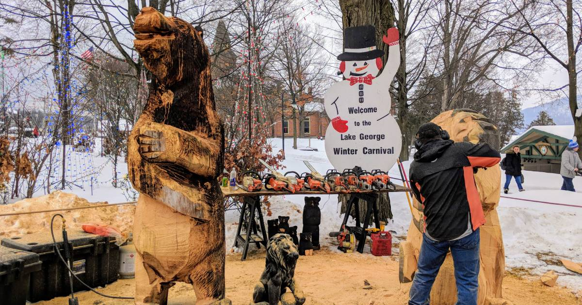 man doing chainsaw carvings at carnival