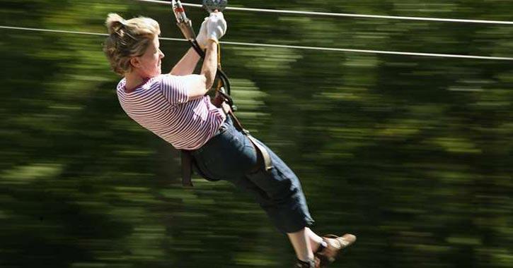 one woman riding down a zipline