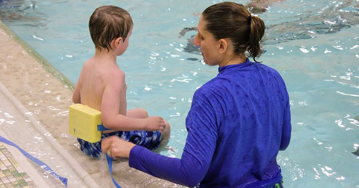 a woman and a little boy in a pool