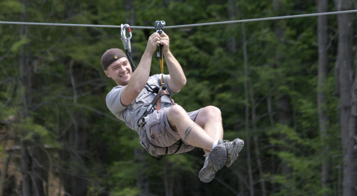 man grinning while on zip line