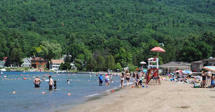 Swimmers and beach goers enjoy a sunny afternoon at Million Dollar Beach in Lake George