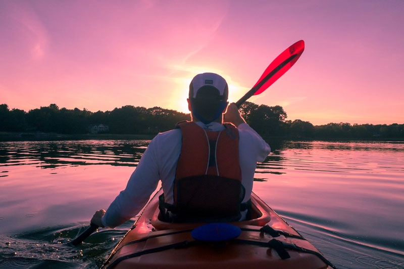 man kayaking into sunset