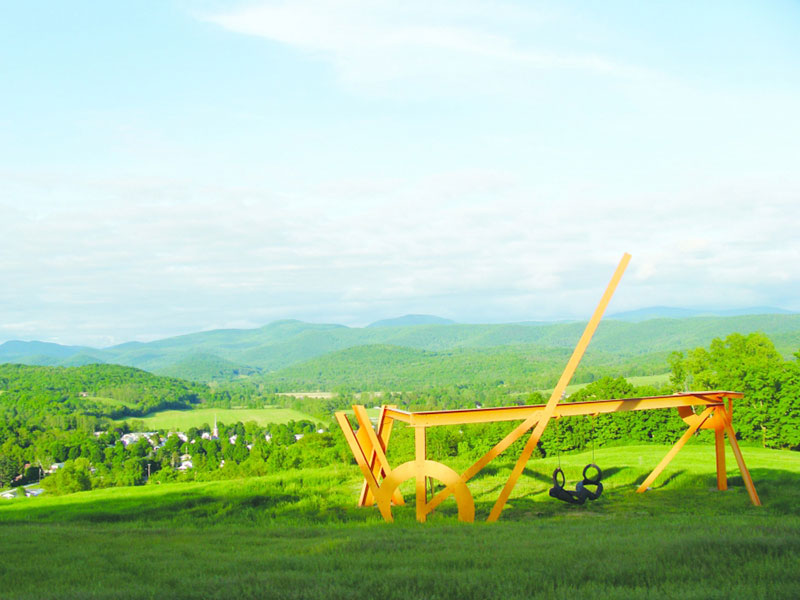 metal sculpture in a field overlooking other fields and mountains