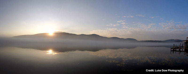 sunrise behind the mountains overlooking lake george with mist on the lake