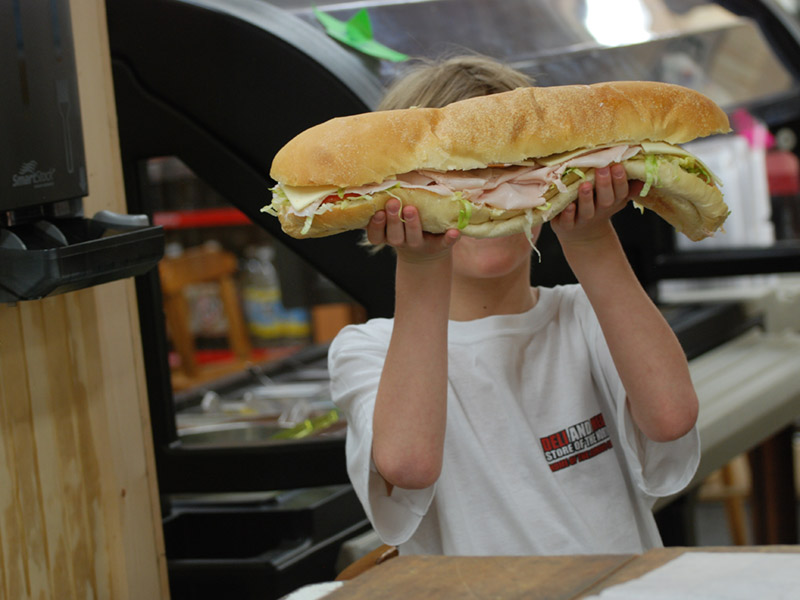 child holding up a big turkey sub