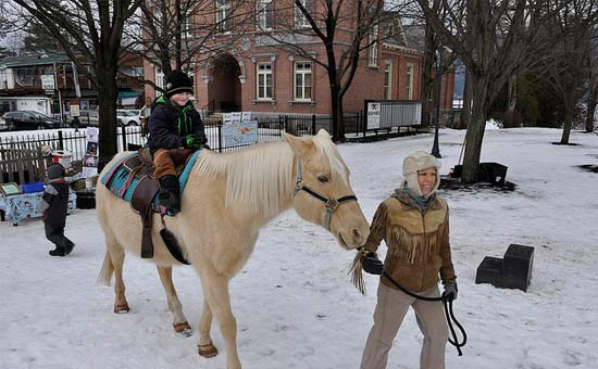 young boy riding horse at winter carnival
