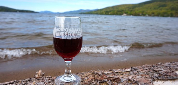 glass with red wine on shore of lake george