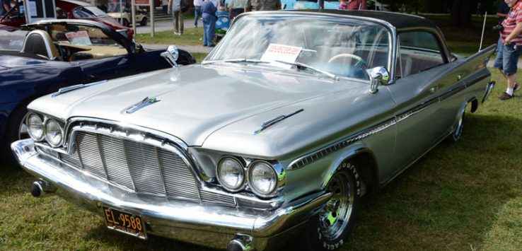 a silver classic car at a car show