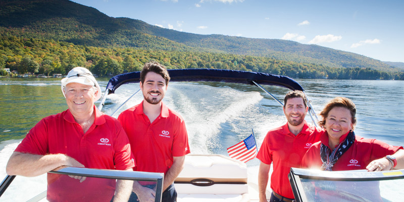 family of four, parents and adult sons, on a boat in Lake George