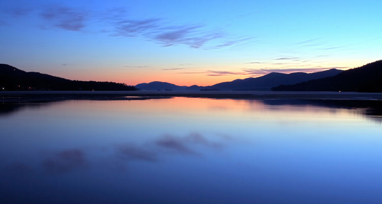 a sunset on lake george with wisps of cloud