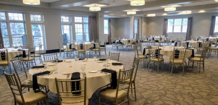 a ballroom set up for an event with circular tables, chairs, etc.
