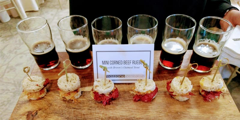 a catering tray of mini corned beef Ruebens with small glasses of stout